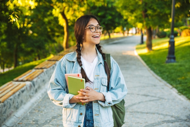 Feliz jovem estudante adolescente carregando mochila e livros enquanto caminha ao ar livre no parque