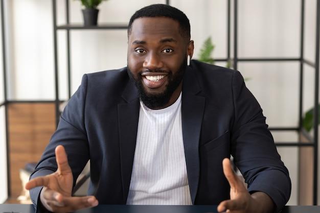 Feliz jovem estudante afro-americano ou empresário participar de negociações virtuais distantes por meio de teleconferência em casa. conceito de videochamada