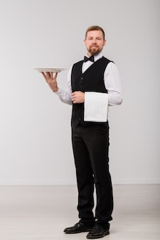 Feliz jovem garçom em um terno elegante e gravata borboleta segurando uma toalha branca limpa e um prato para o hóspede do restaurante