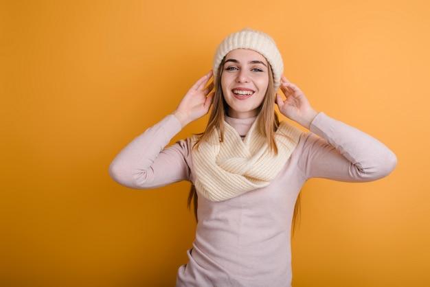 Feliz, jovem garota de chapéu e cachecol posando no estúdio em fundo laranja