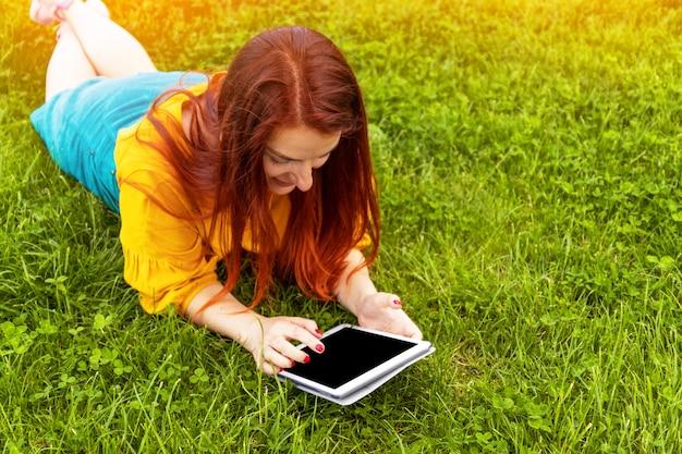 Feliz jovem garota ruiva em uma jaqueta amarela e saia verde está deitado na grama e usando um tablet