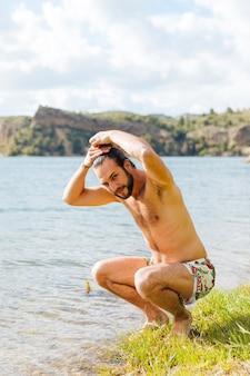 Feliz, jovem, homem barbudo, molhando, cabelo, ligado, lago