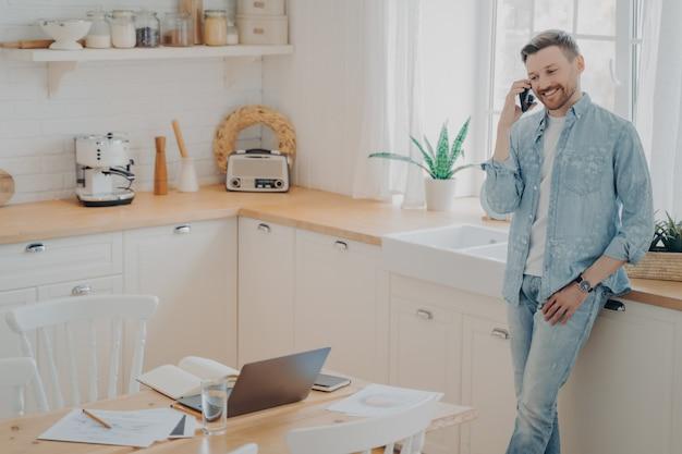 Feliz jovem homem branco segurando o celular enquanto conversa com o cliente, em uma cozinha moderna e apreciando uma boa conversa de negócios enquanto trabalha longe de casa