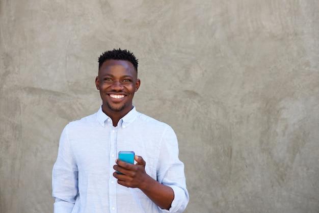 Feliz, jovem, homem preto, com, telefone móvel, ficar, por, parede