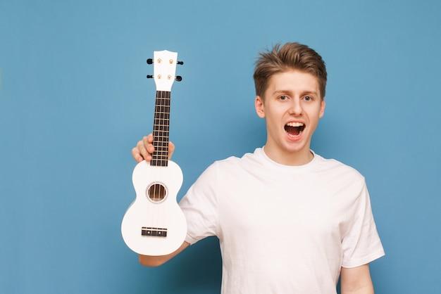 Feliz jovem isolado em azul com ukulele na mão