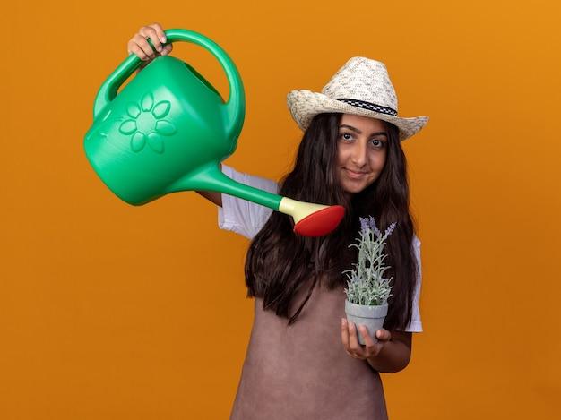 Feliz jovem jardineira com avental e chapéu de verão segurando um regador e uma planta em um vaso com um sorriso no rosto regando uma planta em pé sobre a parede laranja