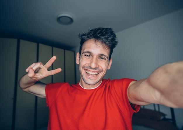 Feliz jovem leva selfie retrato em casa interior.