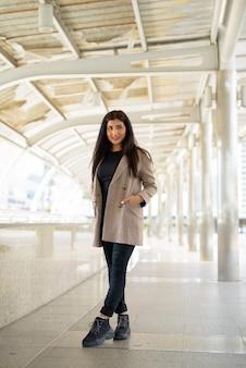 Feliz jovem linda empresária indiana pensando na cidade