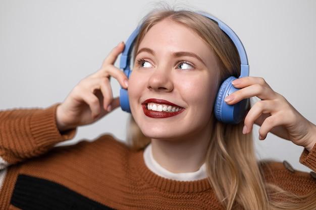 Feliz jovem loira com lábios vermelhos brilhantes, apreciando a música favorita enquanto ouve em fones de ouvido.