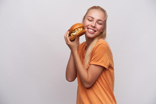 Feliz jovem loira de cabelos compridos com penteado casual, mantendo o saboroso hambúrguer fresco nas mãos e sorrindo alegremente com os olhos fechados, em pé contra um fundo branco
