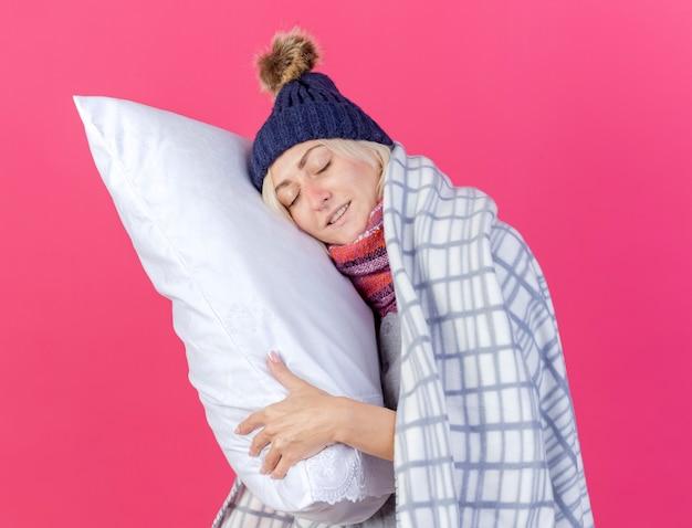 Feliz jovem loira doente com chapéu de inverno e lenço embrulhado em xadrez segura e coloca a cabeça no travesseiro isolado na parede rosa