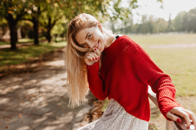 Feliz jovem loira no moderno suéter vermelho e saia branca, sorrindo no outono park. menina elegante com maquiagem natural posando ao ar livre.