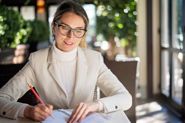 Feliz, jovem, loiro, mulher, em, óculos, trabalhando, um restaurante