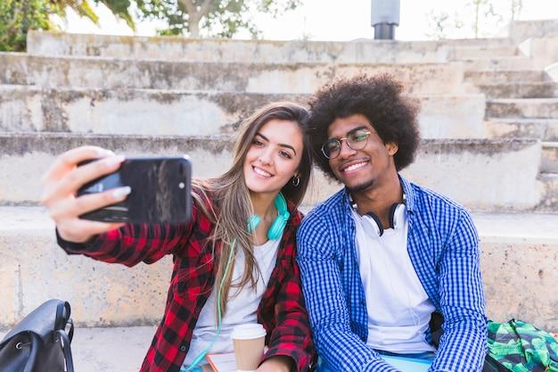 Feliz, jovem, macho fêmea, estudante, levando, selfie, ligado, telefone móvel, em, ao ar livre