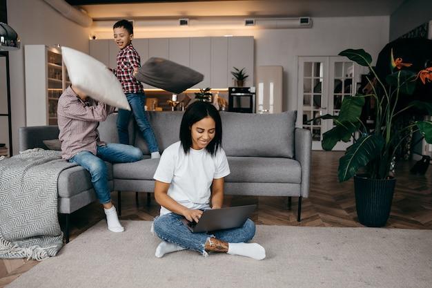 Feliz jovem mãe africana trabalhando em casa com um laptop e se adaptando a filhos barulhentos e ativos lutando contra almofadas no sofá