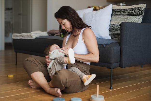 Feliz jovem mãe amamentando um bebê pequeno dentro de casa, em casa, o conceito de amamentação.