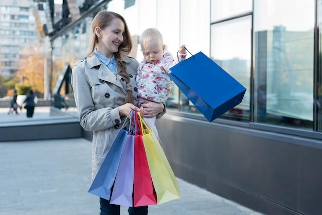Feliz jovem mãe com filha nos braços e sacos de compras na mão.