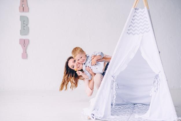 Feliz jovem mãe com seu filho sorridente parece fora da tenda de uma criança na sala de luz.