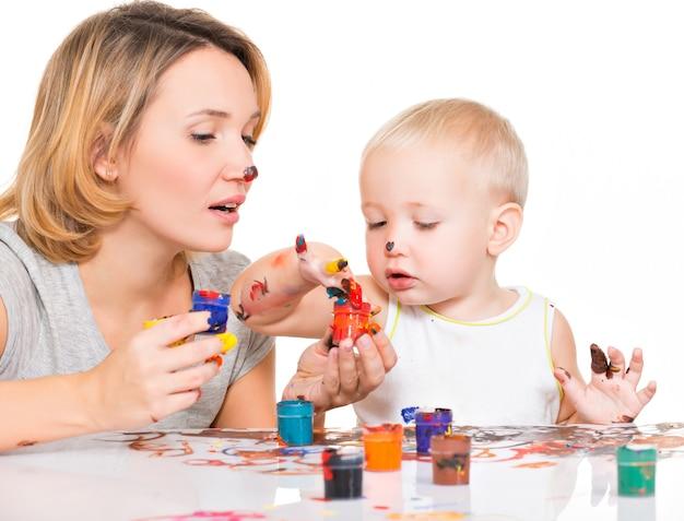 Feliz jovem mãe com uma criança pintar por mãos isoladas em branco.