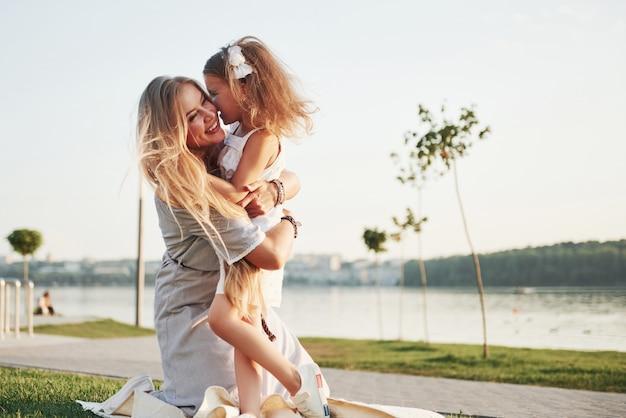Feliz jovem mãe com uma filha brincalhão em um parque perto da água