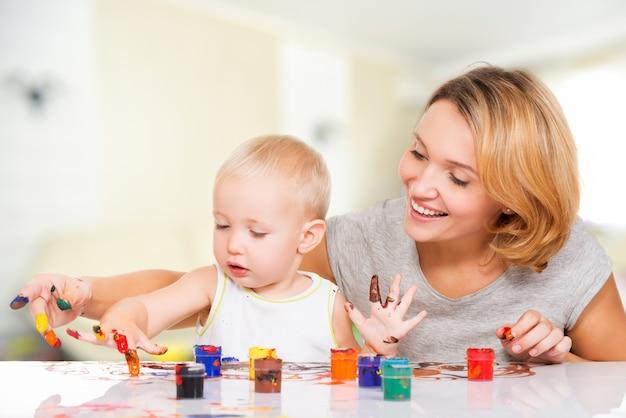 Feliz jovem mãe com uma pintura de bebê pelas mãos em casa.