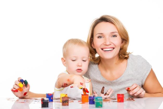Feliz jovem mãe com uma pintura de bebê pelas mãos - isoladas em branco.