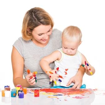 Feliz jovem mãe com uma pintura de bebê por mãos isoladas em branco.