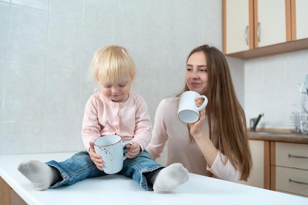Feliz jovem mãe e filha estão sentados à mesa de madeira na cozinha e segurando copos brancos.