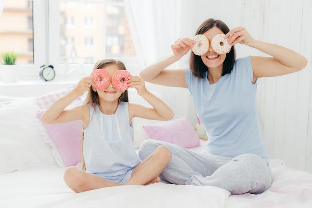 Feliz, jovem mãe e filha se divertir juntos, segure deliciosos donuts doces perto de olhos