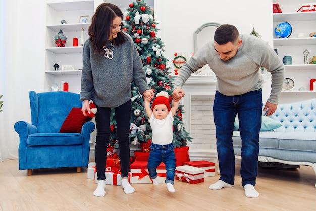 Feliz, jovem, mãe e pai segurando seu doce bebê pelas mãos e levantando-os alto na sala decorada para comemorar o natal