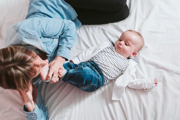 Feliz jovem mãe e seu filho deitado na cama e sorrindo