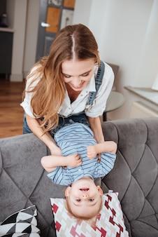 Feliz jovem mãe e seu filho rindo e se divertindo no sofá em casa
