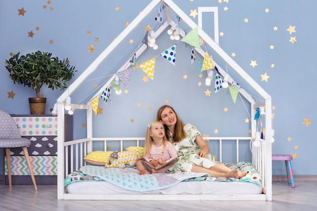 Feliz jovem mãe e sua filha bonita olhando para cima enquanto está sentado na cama de casa bonita