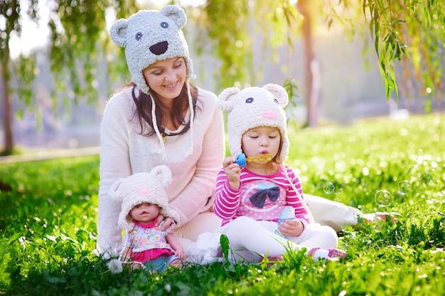 Feliz jovem mãe e sua filha brincando no parque de verão