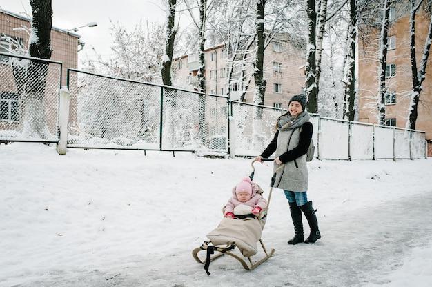 Feliz jovem mãe ficar com o bebê e um trenó de crianças ao ar livre no inverno de fundo.
