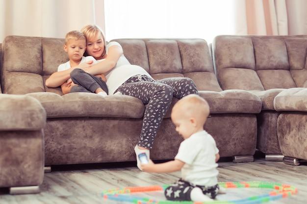 Feliz jovem mãe grávida brincando com seus dois filhos meninos no chão de casa