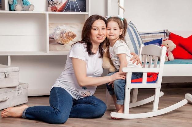 Feliz jovem mãe grávida com uma menina de três anos no quarto das crianças e olhando para a câmera. família adorável, mãe e filha em casa e brincar. momentos familiares atmosféricos do bebê. copie o espaço
