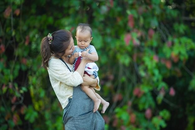 Feliz jovem mãe jogando e se divertindo com seu filho pequeno
