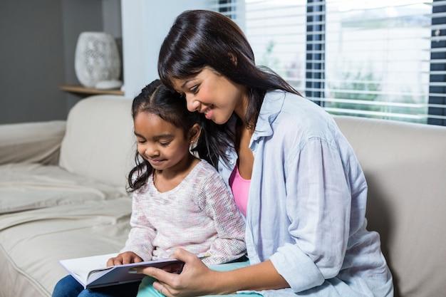 Feliz jovem mãe lendo um livro com sua filha