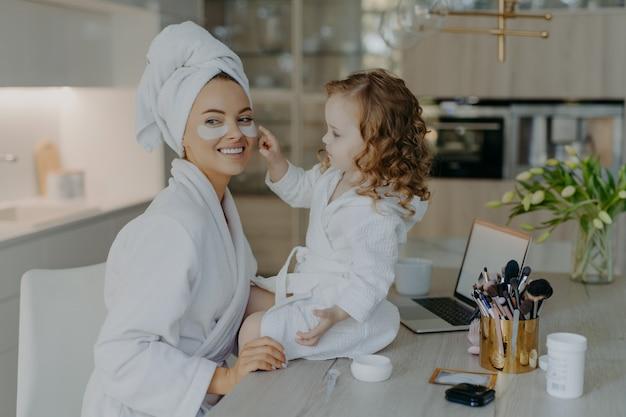 Feliz jovem mãe professora sua filha para fazer maquiagem.