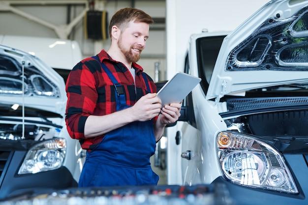 Feliz jovem mecânico ou técnico em roupas de trabalho olhando para a tela do tablet enquanto procura dados técnicos