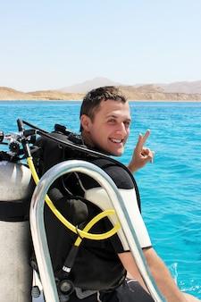 Feliz jovem mergulhador em um terno para mergulho está se preparando para mergulhar
