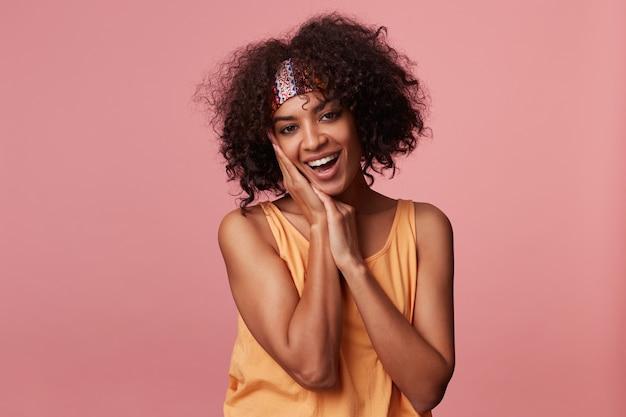 Feliz jovem morena encaracolada com pele escura usando uma bandana colorida e um top laranja claro em pé, sorrindo alegremente e mantendo as mãos sob a bochecha
