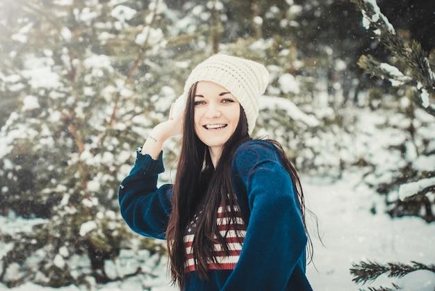Feliz jovem morena jogando bola de neve em winter park