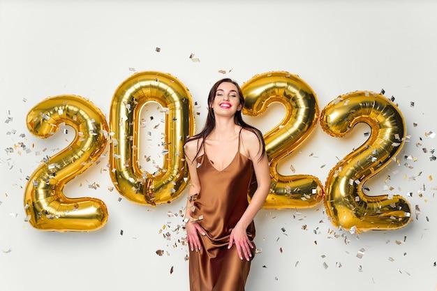 Feliz jovem morena perto de balões dourados na celebração do ano novo de fundo branco usando fa ...
