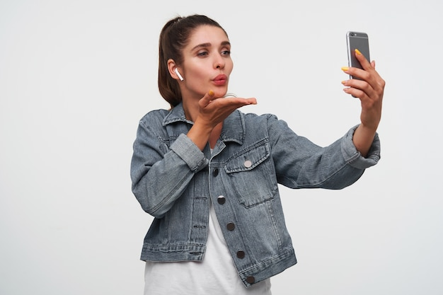 Feliz jovem morena veste camiseta branca e jaquetas jeans, segura smartphone e manda beijo para o videochat. fica sobre fundo branco.