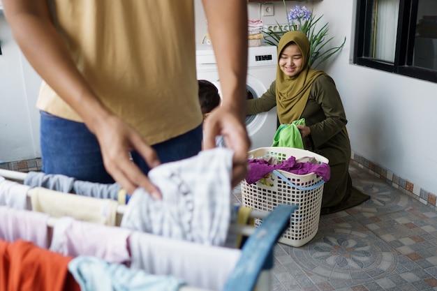 Feliz jovem muçulmana e o marido lavando roupa juntos em casa