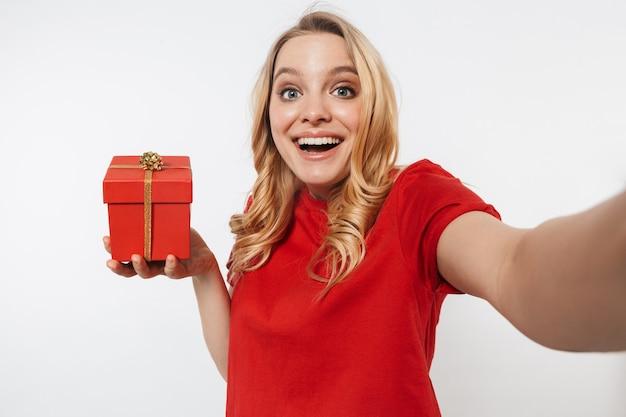 Feliz, jovem, muito bonita, mulher posando isolada sobre uma parede branca, tire uma selfie com a câmera segurando uma caixa de presente