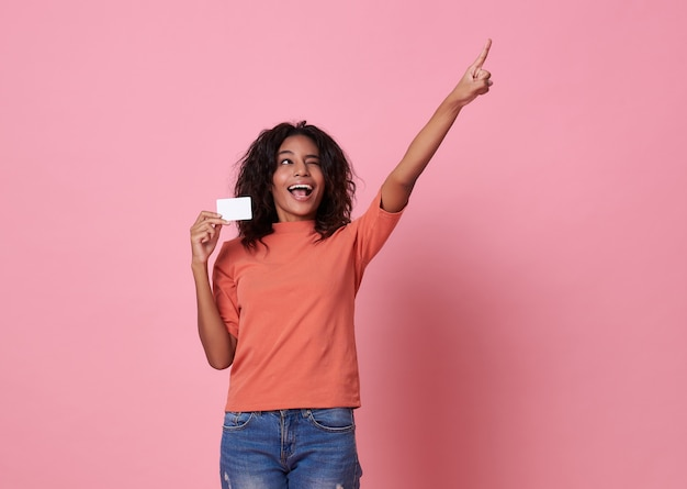 Feliz jovem mulher africana em pé com o dedo apontando no fundo rosa