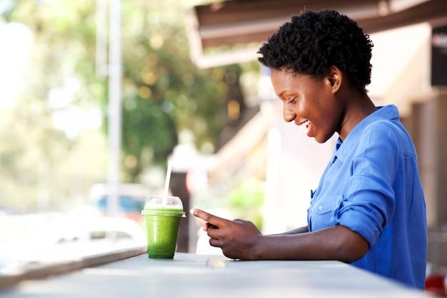Feliz, jovem, mulher africana, sentando, em, café, usando, telefone móvel